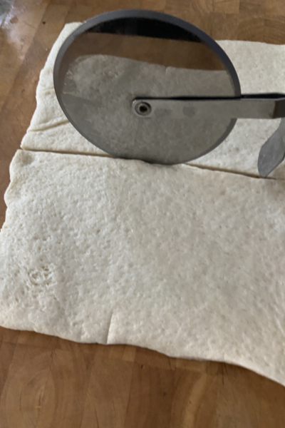 cutting pizza dough